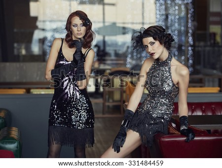 Two girls, models in retro dress in the cafe Retro, style, fashion.