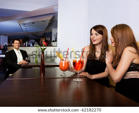 Two girls noticed elegant young man - stock photo