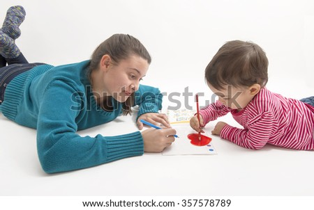 two girls of different ages lying on the floor and drawing isolated on white - stock photo