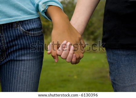 two girls of different ethnicities holding hands....symbolizing unity - stock photo