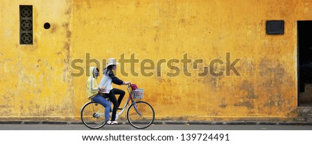 Two Girls on Bicycle with Old Wall in Vietnam - stock photo