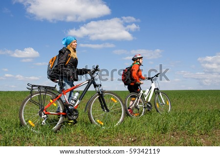 Two girls on bicycles in the countryside, with blue sky. Everyone can ride a bike. Everyone who rides a bike is my friend. - stock photo