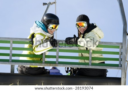 Two girls on chairlift ready to go skiing - stock photo