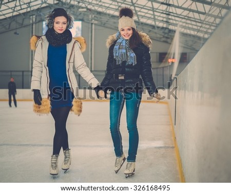 Two girls on ice-skating rink