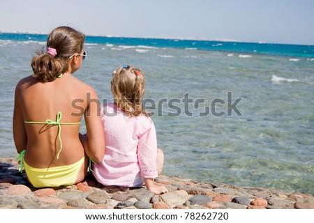 Two girls on seacoast - stock photo