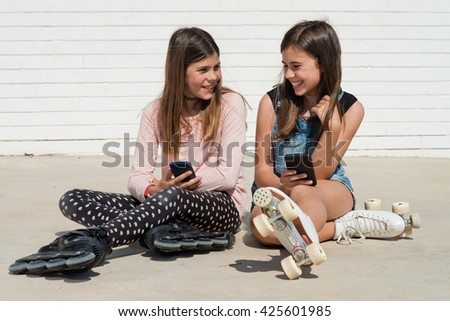 two girls on skates and smartphone laughing