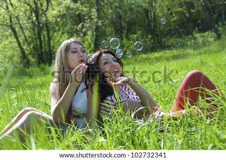 Two girls on the meadow blow bubbles - stock photo