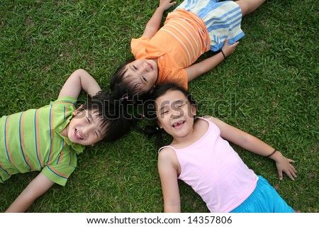 Two girls & one boy lying on the grass - stock photo