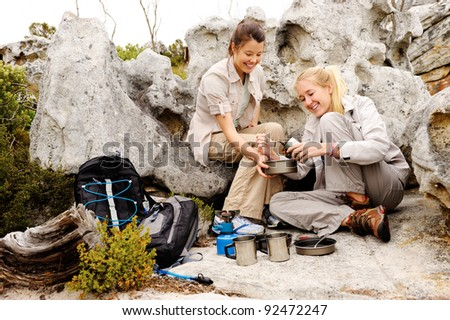 two girls open a can of baked beans while they are camping and hiking in the wilderness - stock photo