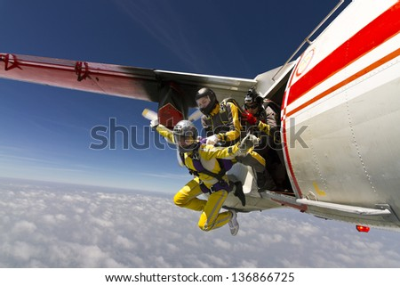 Two girls parachutist jumping out of an airplane. - stock photo