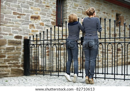 Two girls peeking through gate, rear view - stock photo
