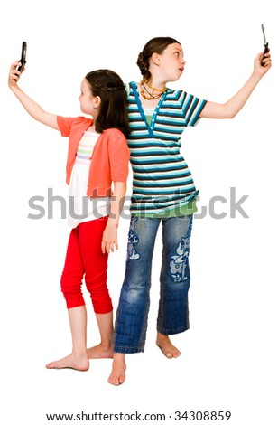 Two girls photo messaging on mobile phones isolated over white - stock photo