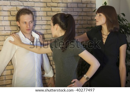 two girls pinned man to the brick wall - stock photo