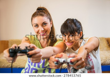Two girls play video games on the joysticks at home. - stock photo