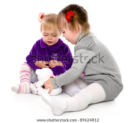 Two girls play with a teddy bear. Isolated on a white background - stock photo