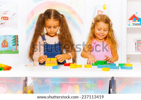 Two girls play with blocks in class