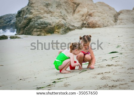 Two girls playing in the sand at the beach