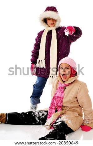 Two girls playing, one dropping snow on the head of another. - stock photo