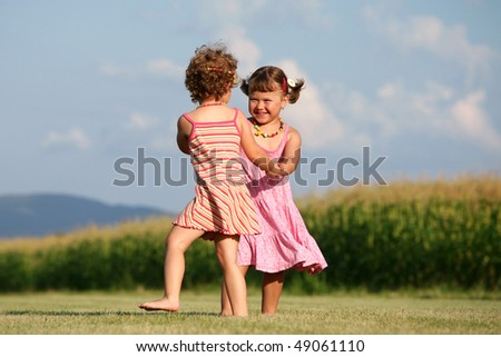 Two girls playing outdoors - stock photo