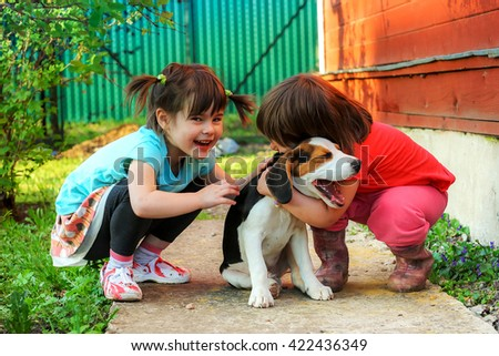 Two girls playing with a beagle puppy. - stock photo