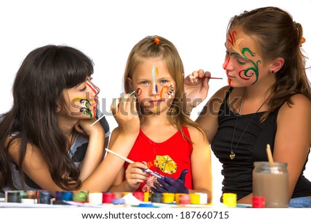 Two girls playing with painting with sister. - stock photo