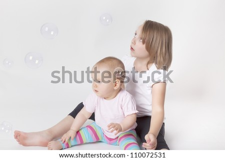 two girls playing with soap bubbles.