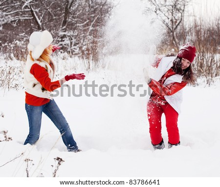 Two  girls plays with snow at winter park - stock photo