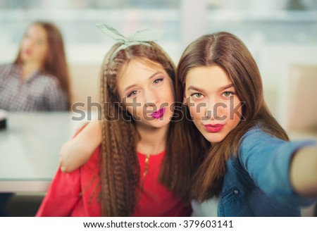 Two girls pouting while taking a selfie photo on mobile phone, selective focus - stock photo