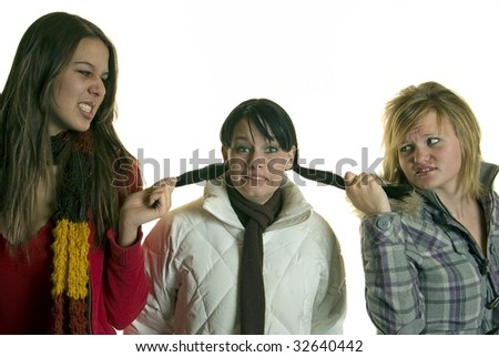 Two girls pull the hair of third girl - stock photo