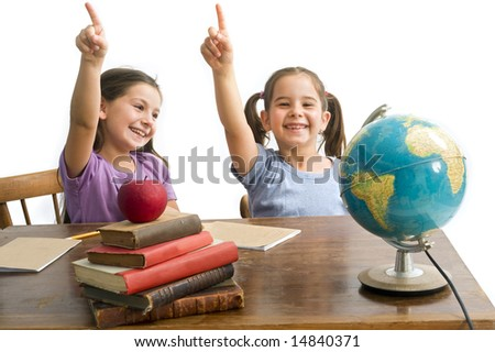 two girls pupels pointing in a class room with table, globe and red apple on a pile of books, Isolated on white - stock photo