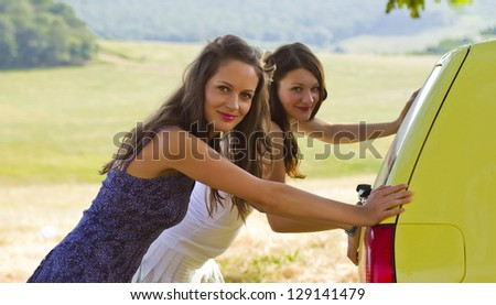 two girls pushing a yellow car in the  fields - stock photo