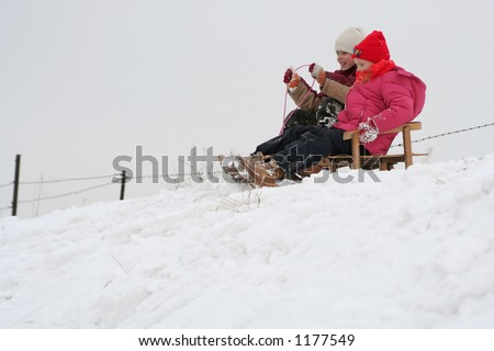 Two girls racing on the sleds - stock photo