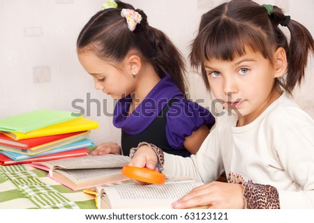 Two girls read books behind a table