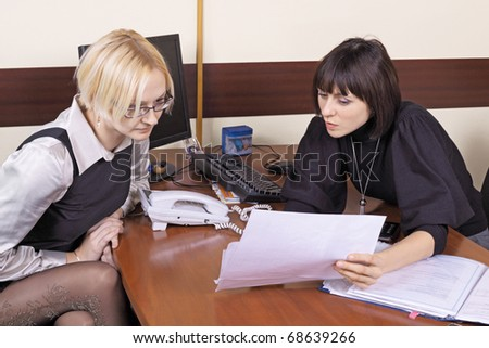 Two girls read documents at office behind a table - stock photo