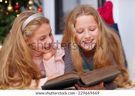 two girls reading a book christmas tree in background - stock photo
