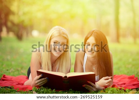Two girls reading book in park