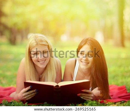 Two girls reading book in park - stock photo