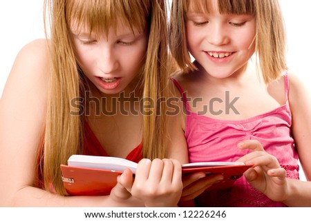 Two girls reading open book - stock photo