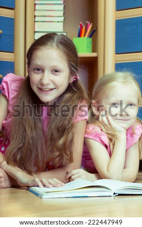 two girls reads book in your room  - stock photo