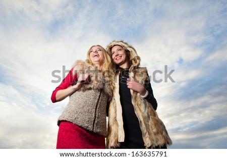 Two girls rejoice on background sky - stock photo