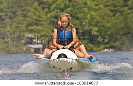 Two girls riding a tube behind a boat.