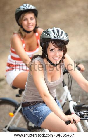 Two girls riding bikes - stock photo