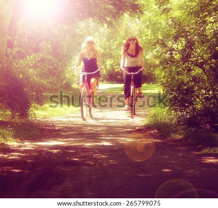 two girls riding bikes on a path in a park full of trees toned with a retro vintage instagram filter effect app or action  - stock photo