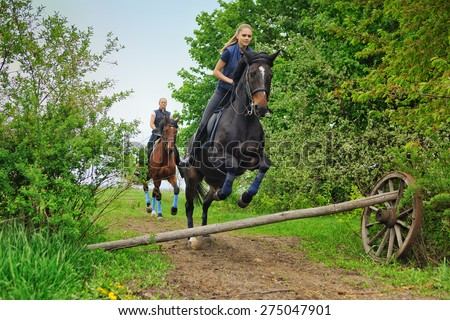 Two  girls riding horses  on countryside - stock photo