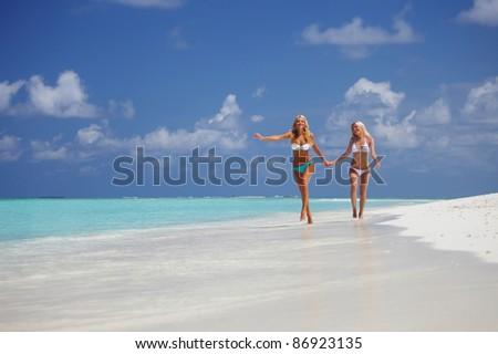 Two girls run along the ocean coast - stock photo