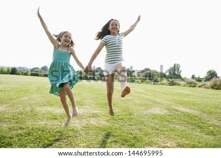 Two girls running and jumping hand in hand through field - stock photo