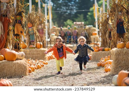 Two Girls Running at the Pumpkin Patch