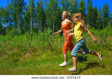 Two girls running on a meadow - stock photo
