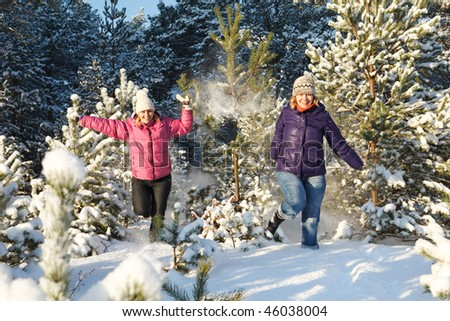 Two girls running through spruce trees covered in snow - stock photo