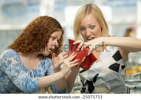 Two girls shake out purse contents in cafe